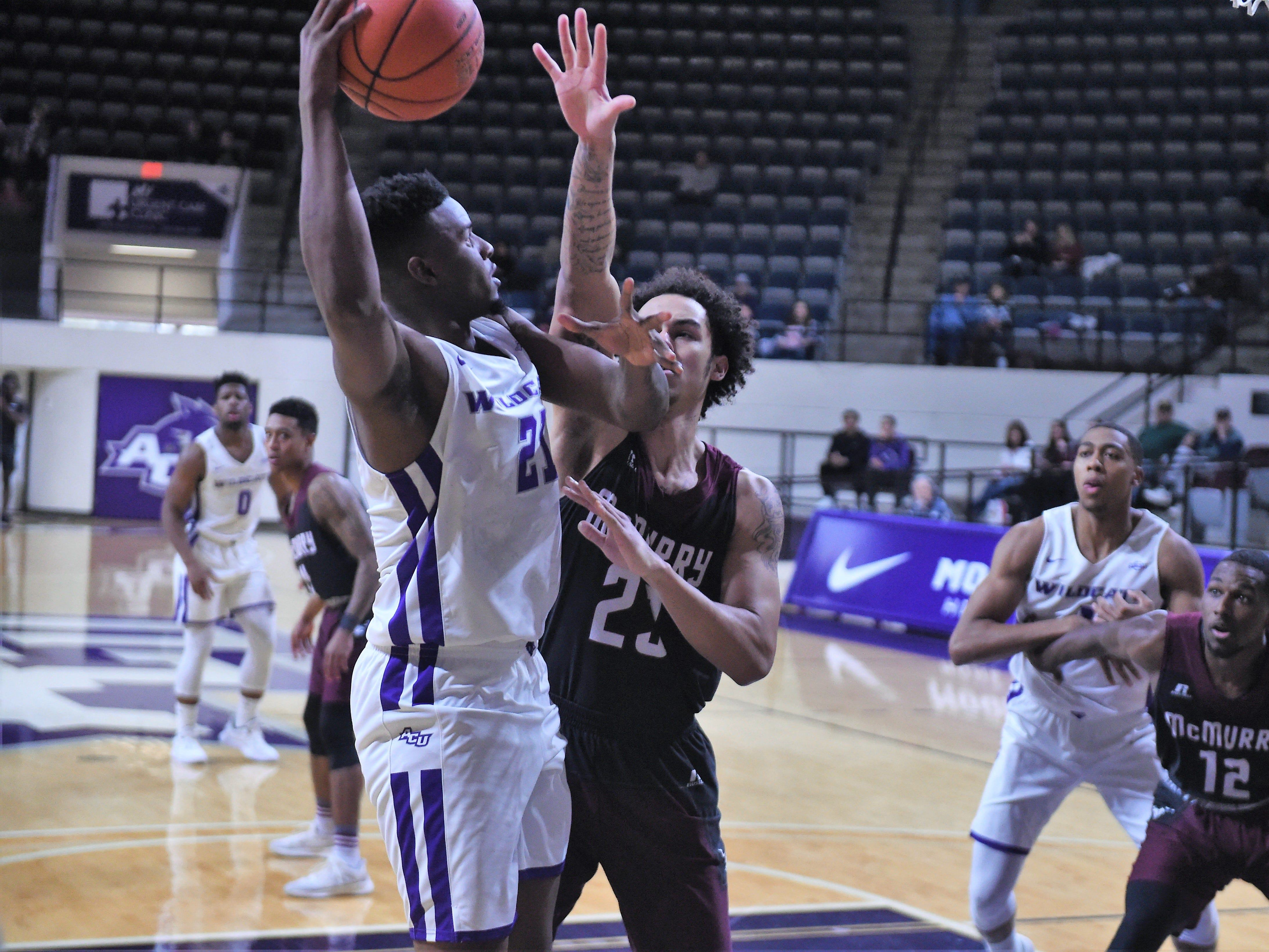 ACU's Jalone Friday (21) goes over McMurry's Jordan Jackson (23) during Saturday's game at Moody Coliseum.