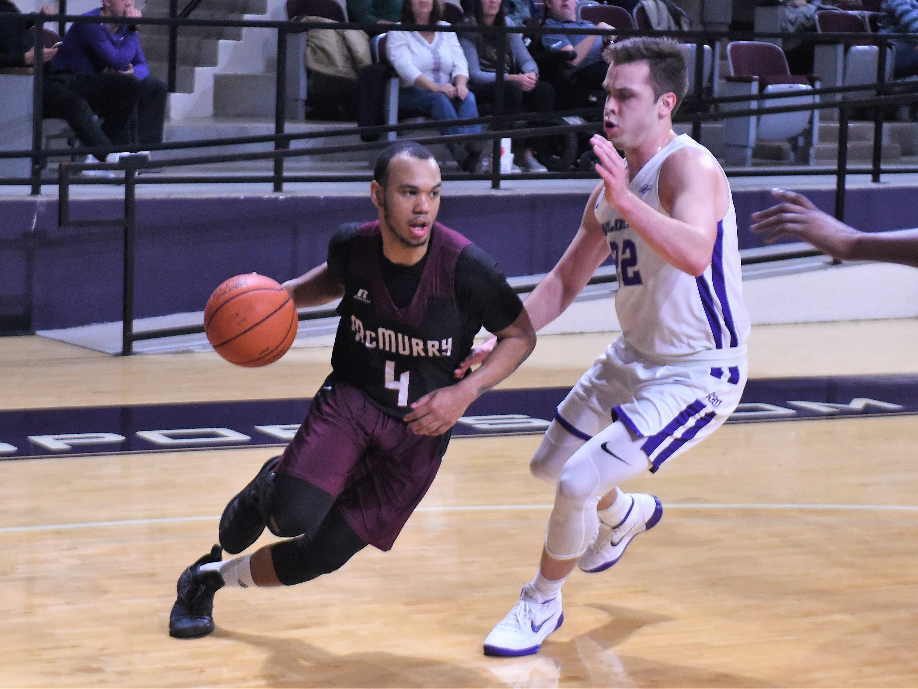 McMurry's Colin Taylor (4) tries to drive past ACU's Chase Cobb (22) during Saturday's game at Moody Coliseum.