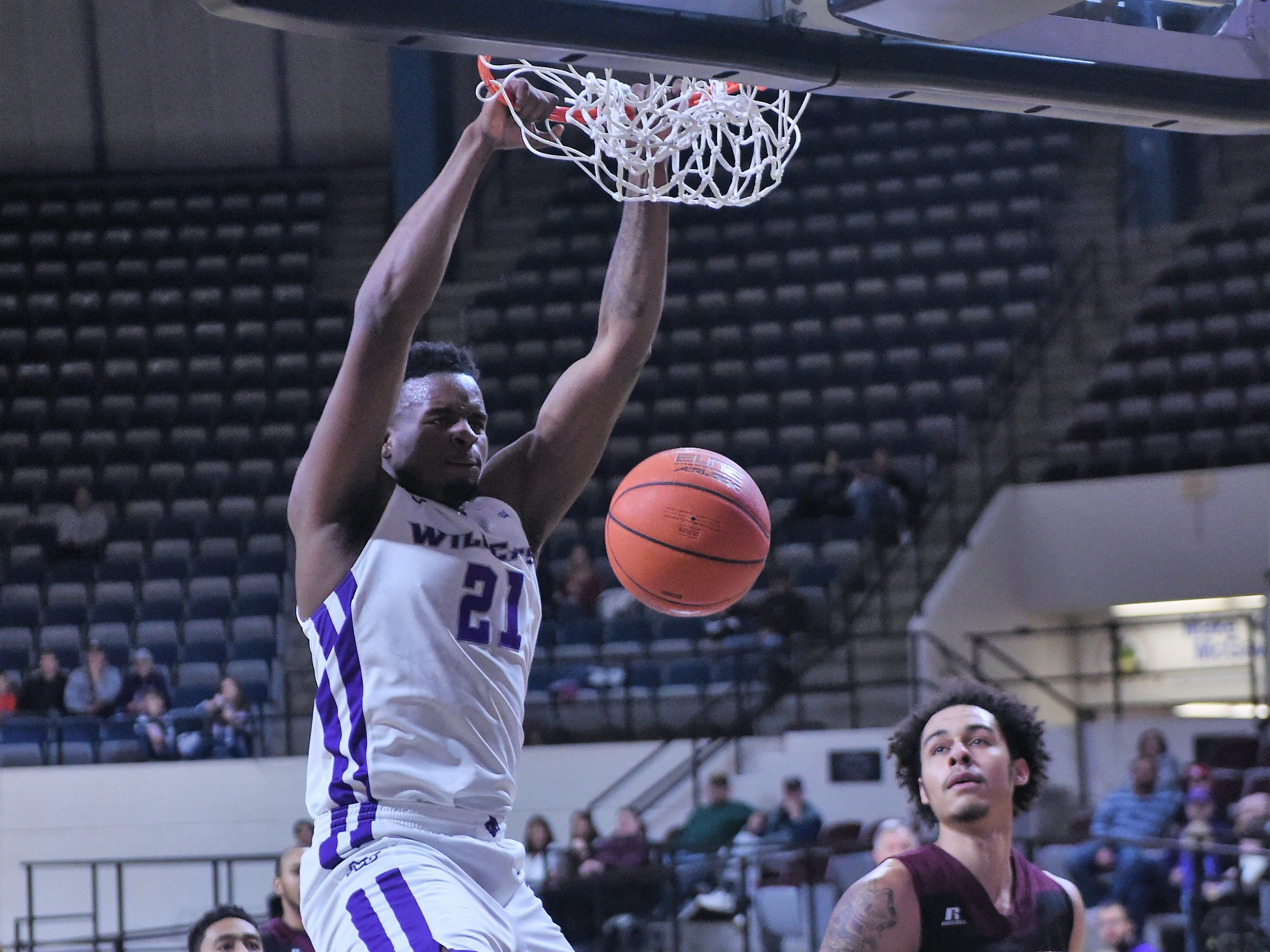 ACU's Jalone Friday (21) finishes off a dunk during Saturday's game against McMurry at Moody Coliseum.