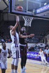 McMurry's Khalil Butler (12) blocks an ACU shot during last season's game at Moody Coliseum. ACU won the game 88-40.
