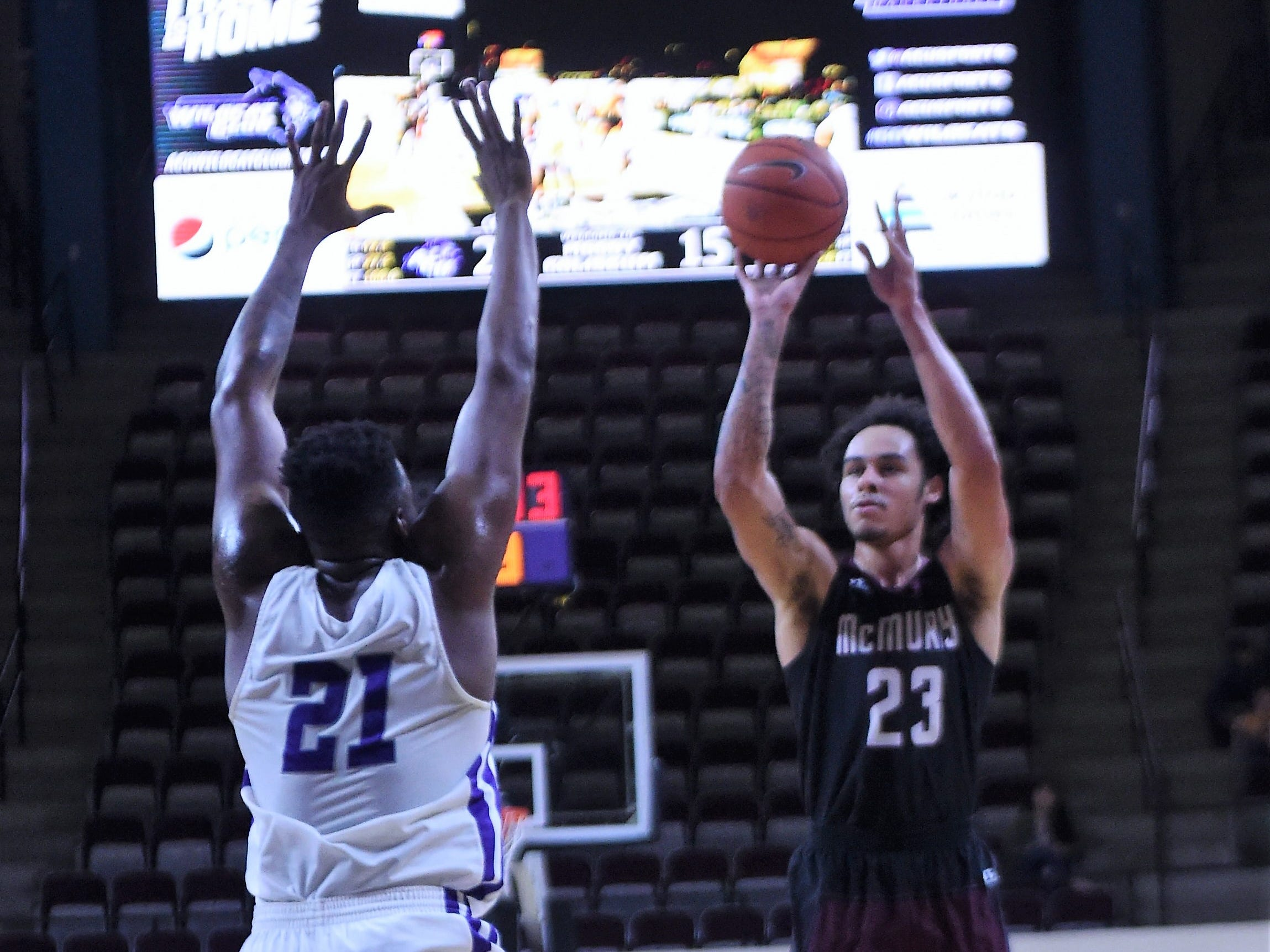 McMurry's Jordan Jackson (23) takes a shot over ACU's Jalone Friday (21) during Saturday's game at Moody Coliseum.