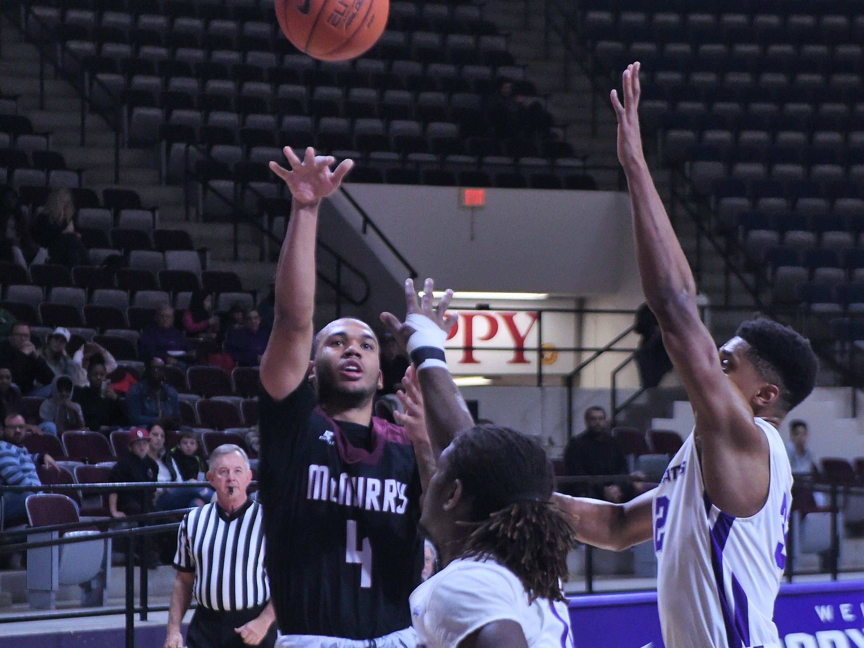 McMurry's Colin Taylor (4) puts up a shot over a pair of ACU defenders during Saturday's game at Moody Coliseum.