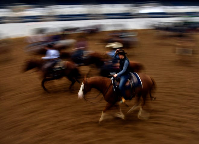Riders are blurred as they constantly circle their horses on the north side of the Taylor County Coliseum, warming them up Friday. The Abilene Winter Circuit Cutting finishes Thursday.
