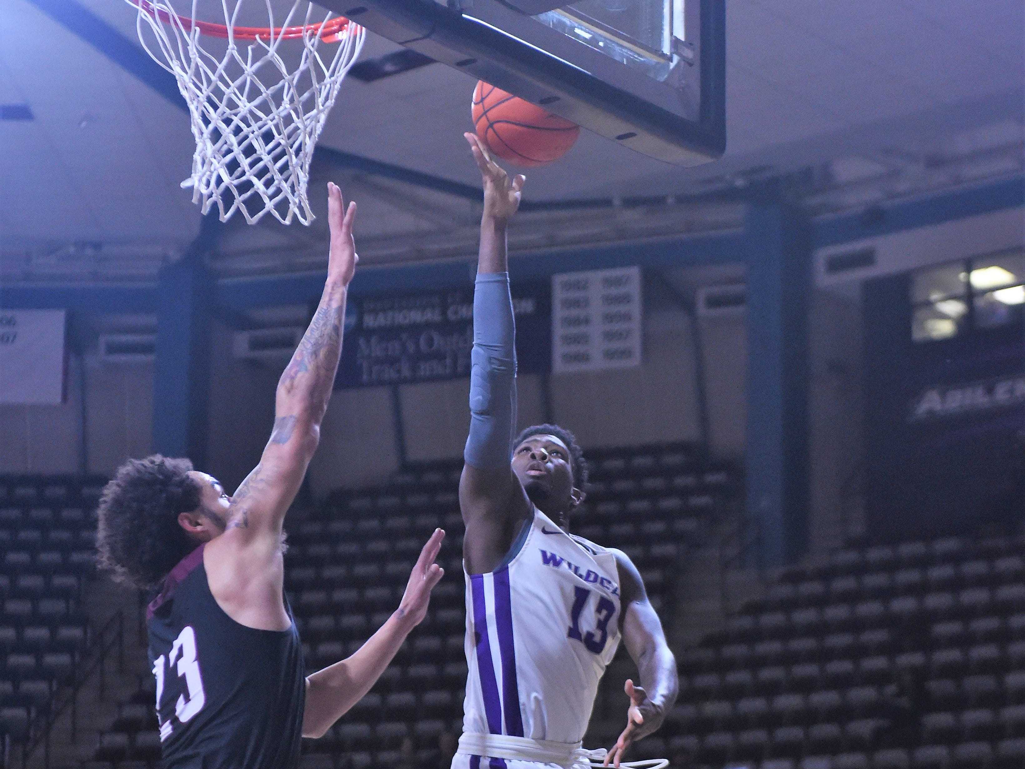 ACU's B.J. Maxwell (13) shoots a lay-up over McMurry's Jordan Jackson (23) during Saturday's game at Moody Coliseum.