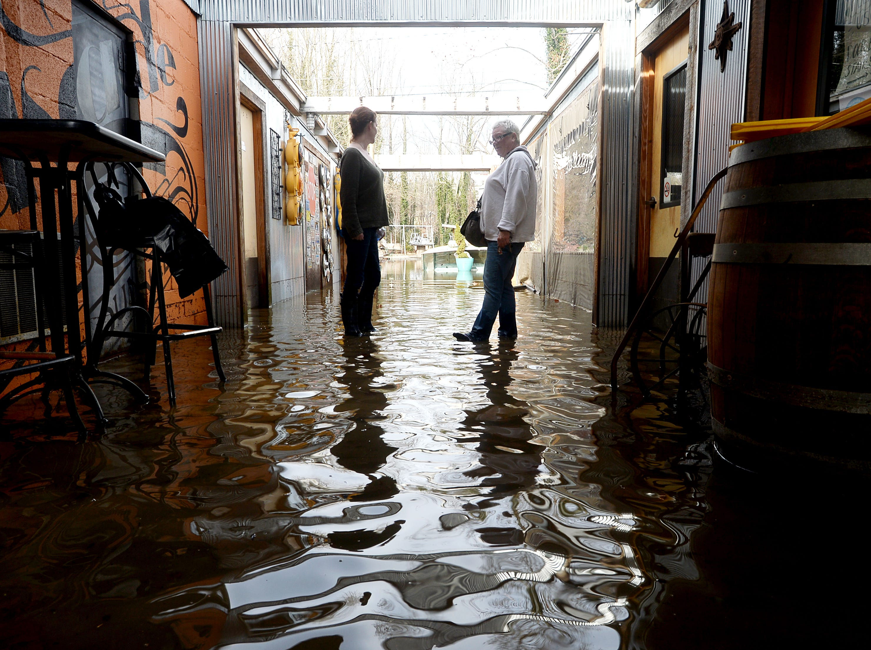 Jennifer Pittman, left, and Terri Terrell wade through water between the Cascade Lounge and HomeGrown in West Asheville Dec. 29, 2018.