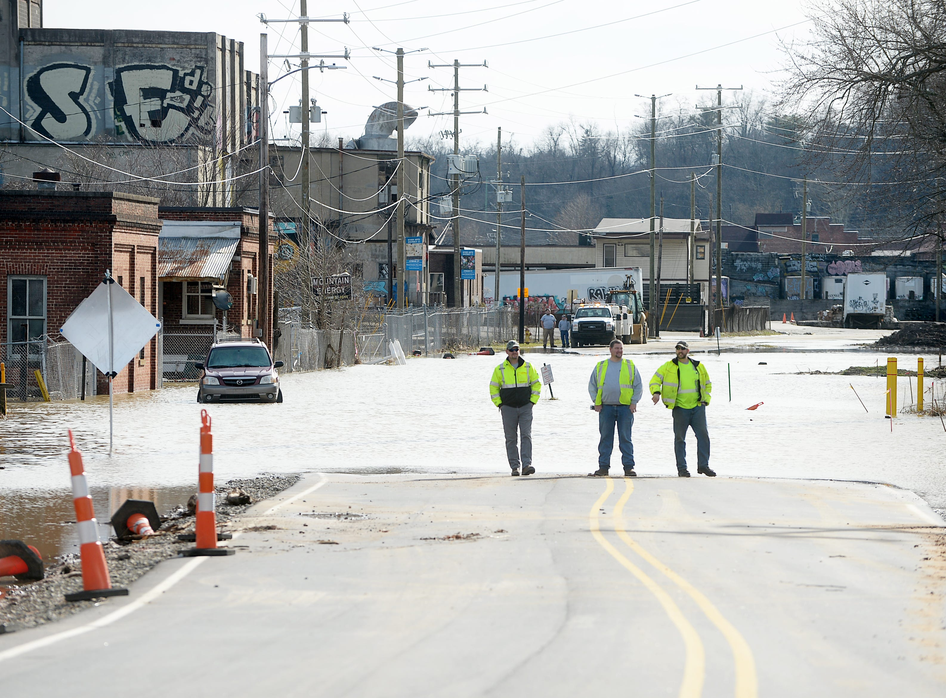 Asheville City employees from left, John White, Jeremy Hyatt and Kyle Hoehn survey the scene as the French Broad River overflows onto Lyman Street in Asheville Dec. 29, 2018.