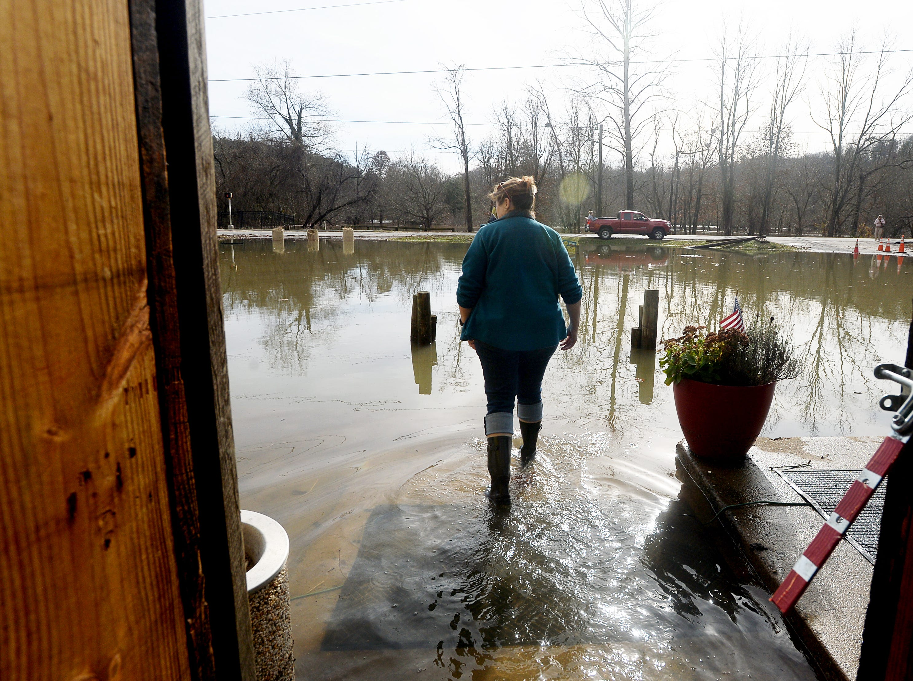 Jolene Fleischbein, owner of Cascade Lounge, walks out of the bar and restaurant complex and into a flooded parking lot Dec. 29, 2018.