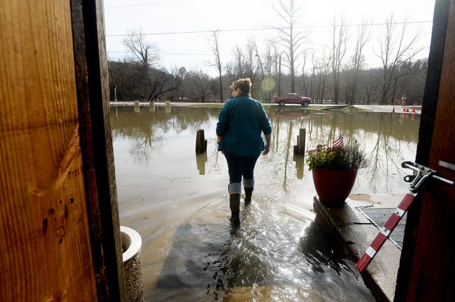 Jolene Fleischbein, owner of Cascade Lounge, walks out of the Asheville bar and restaurant complex Saturday and into a flooded parking lot near the French Broad River.