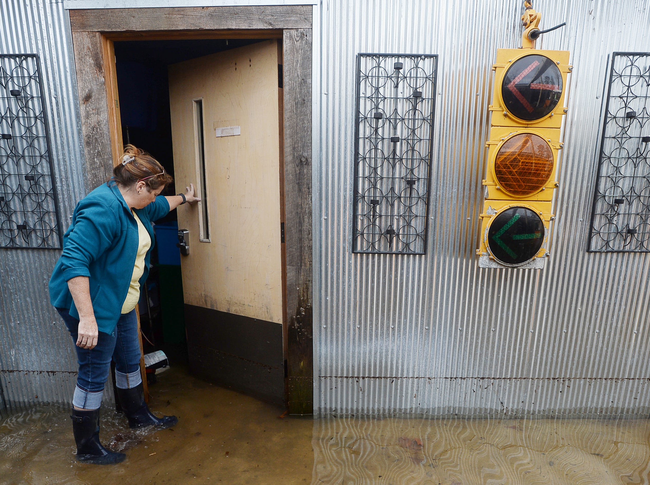 "Jolene Fleischbein, owner of Cascade Lounge, opens the door to a storage room as she wades through water from an overflowing Moore Creek Dec. 29, 2018. It is the third time this year the bar has flooded. ""It's been a hard year,"" said Fleischbein, who said this weekend's flooding was the worst this year."
