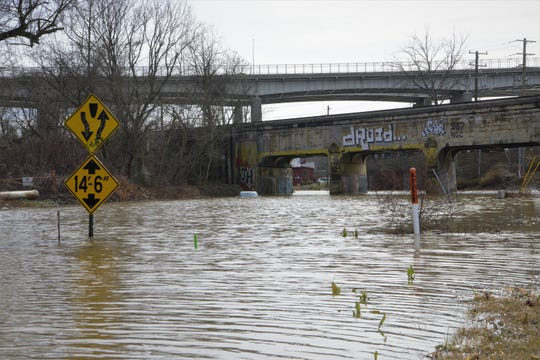 An abandoned car sits in several feet of water on Riverside Drive, which runs parallel to the French Broad River.