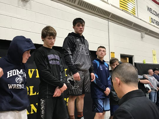 Walton/Delhi senior Caleb Robinson stands atop the awards podium after winning the 120-pound title Friday in the Windsor Christmas Tournament.