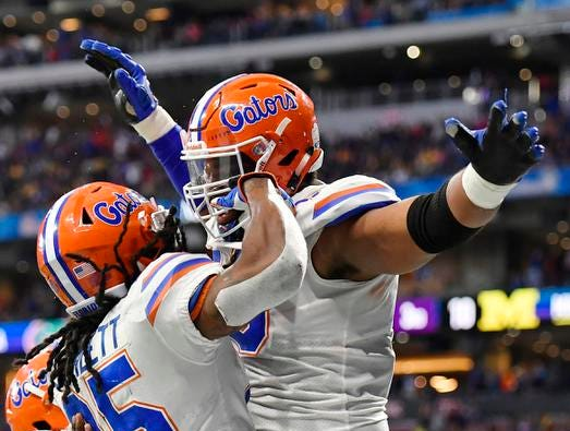 Florida running back Jordan Scarlett (25) celebrates his touchdown with Florida offensive lineman Martez Ivey (73) during the first half of the Peach Bowl NCAA college football game against Michigan, Saturday, Dec. 29, 2018, in Atlanta. (AP Photo/Mike Stewart)