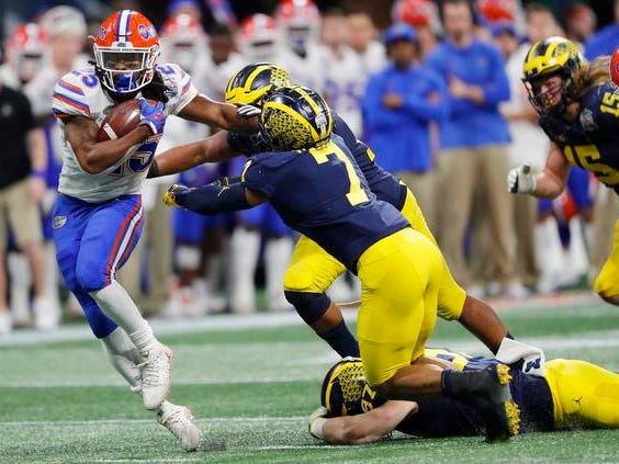 Florida running back Jordan Scarlett (25) runs by Michigan linebacker Khaleke Hudson (7) during the first half of the Peach Bowl NCAA college football game, Saturday, Dec. 29, 2018, in Atlanta. (AP Photo/John Bazemore)