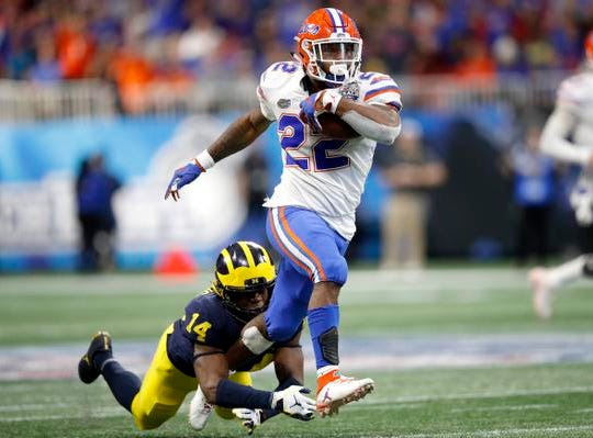 ATLANTA, GEORGIA - DECEMBER 29:  Lamical Perine #22 of the Florida Gators escapes the tackle attempt of Josh Metellus #14 of the Michigan Wolverines and runs for a fourth quarter touchdown during the Chick-fil-A Peach Bowl at Mercedes-Benz Stadium on December 29, 2018 in Atlanta, Georgia. (Photo by Joe Robbins/Getty Images)