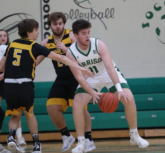 Harrison forward Connor Kinnett (11) gets a rebound near Taylor players Blake Brunswick and Lucas Picklesimer during their basketball game Friday, Dec. 28, 2018.