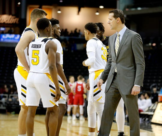NKU head coach John Brannen talks with Zaynah Robinson and other players  during a timeout.