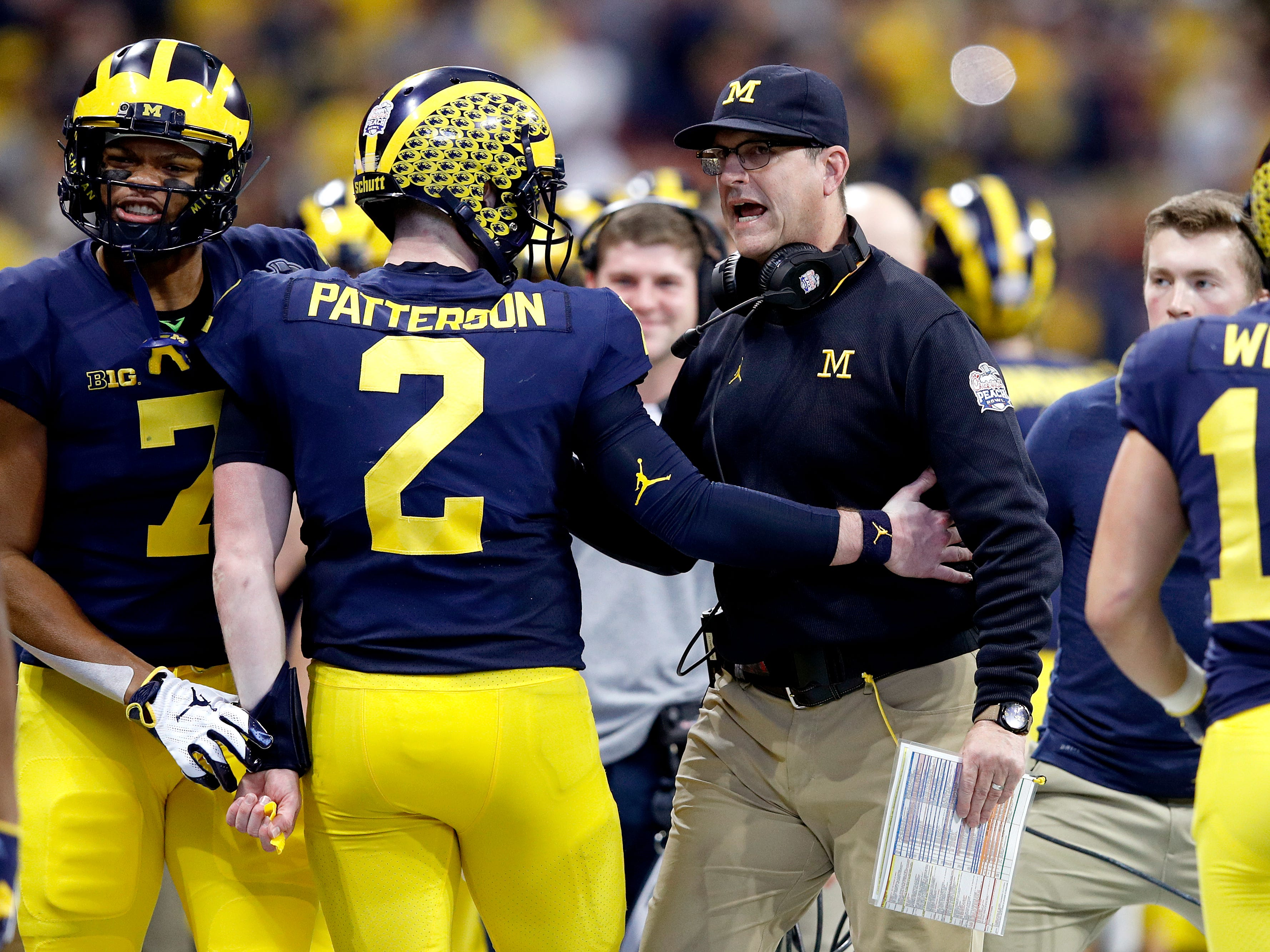 Michigan quarterback Shea Patterson  and coach Jim Harbaugh celebrate a touchdown against Florida during the Peach Bowl on Saturday, Dec. 29, 2018, in Atlanta.