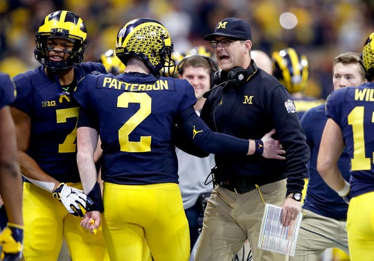 Shea Patterson and coach Jim Harbaugh celebrate a touchdown against Florida during the Peach Bowl.