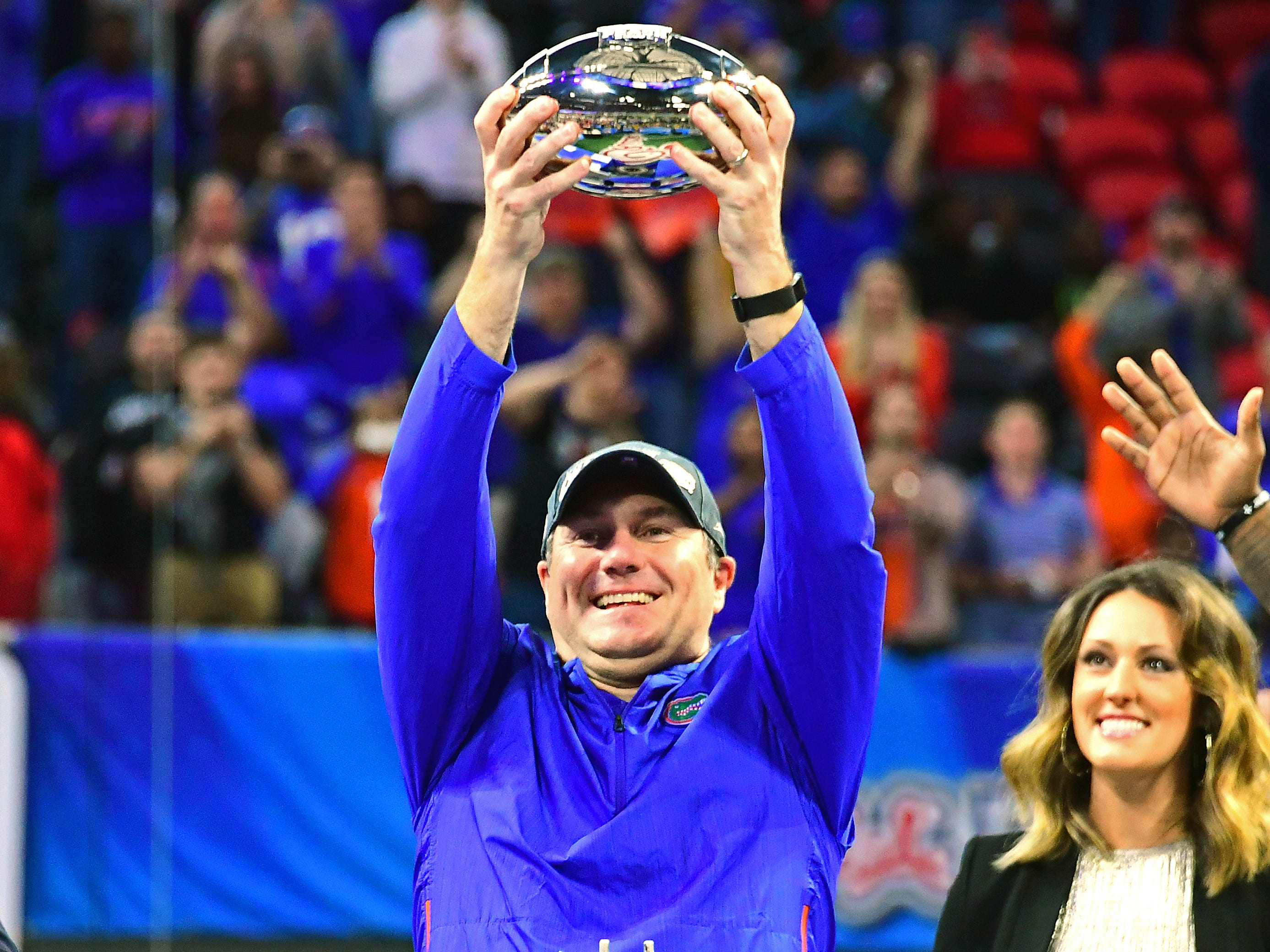 Florida coach Dan Mullen hold the trophy after U-M's 41-15 loss in the Peach Bowl on Saturday, Dec. 29, 2018, in Atlanta.