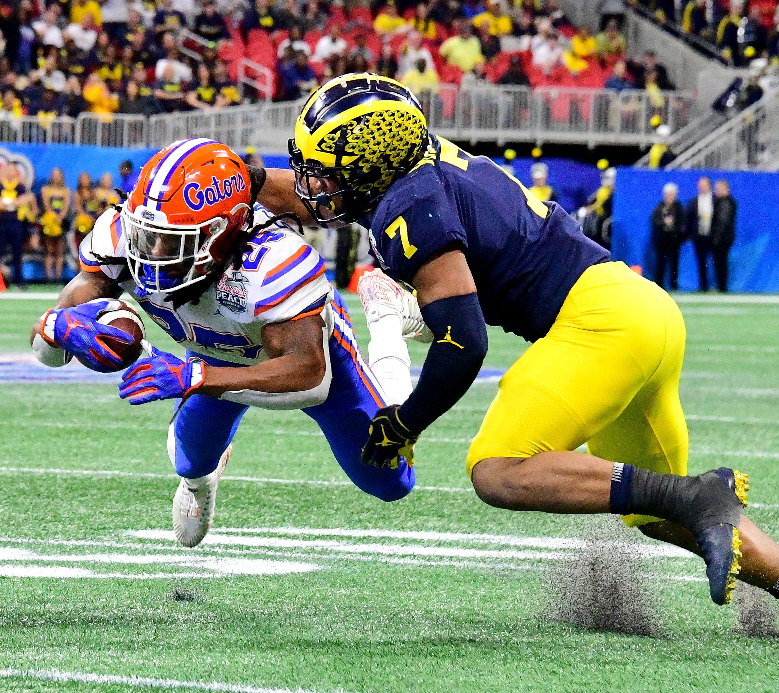 Michigan linebacker Khaleke Hudson makes a tackle in the Peach Bowl.
