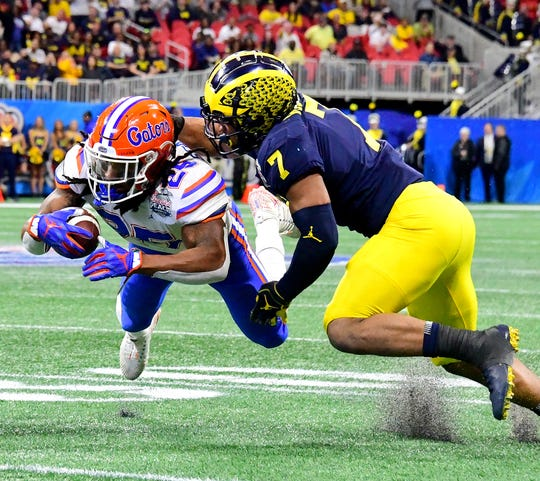 Florida running back Jordan Scarlett is tackled by Michigan linebacker Khaleke Hudson in the second quarter during the Peach Bowl on Saturday, Dec. 29, 2018, in Atlanta.