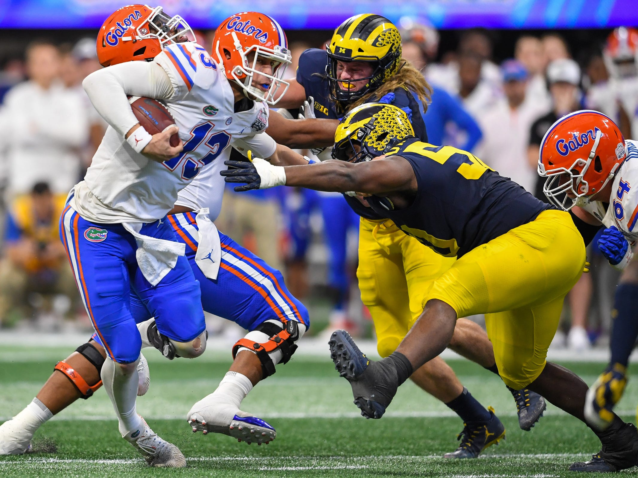 Florida quarterback Feleipe Franks runs against Michigan defensive lineman Michael Dwumfour during the first half of the Peach Bowl on Saturday, Dec. 29, 2018, in Atlanta.