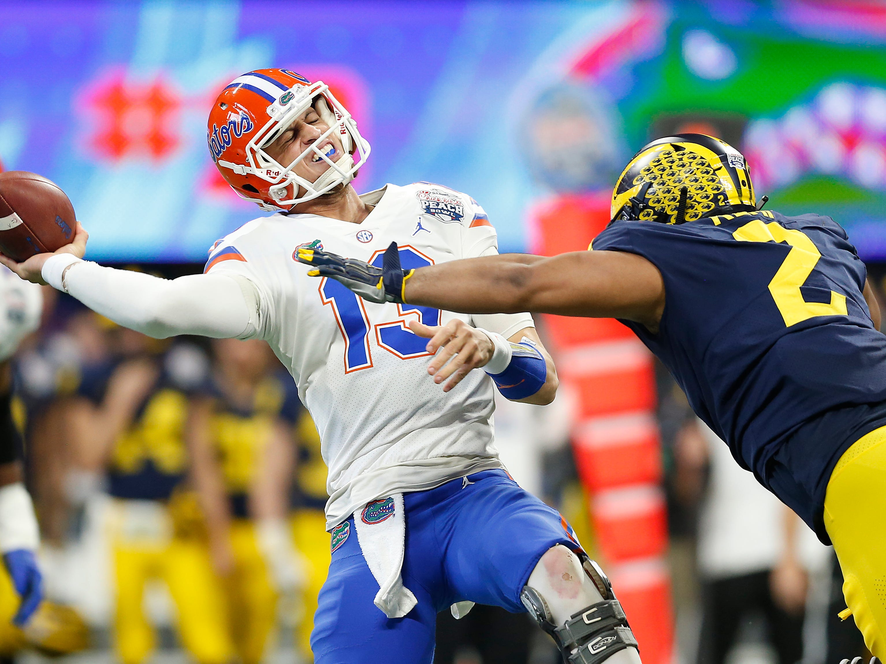 Florida QB Feleipe Franks throws under pressure from Michigan defensive lineman Carlo Kemp in the first quarter of the Peach Bowl on Saturday, Dec. 29, 2018, in Atlanta.