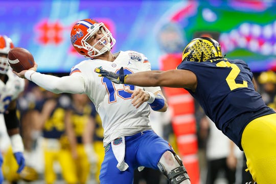 Florida QB Feleipe Franks throws under pressure from Michigan defensive lineman Carlo Kemp in the first quarter of the Peach Bowl on Saturday, Dec. 29, 2018, in Atlanta.