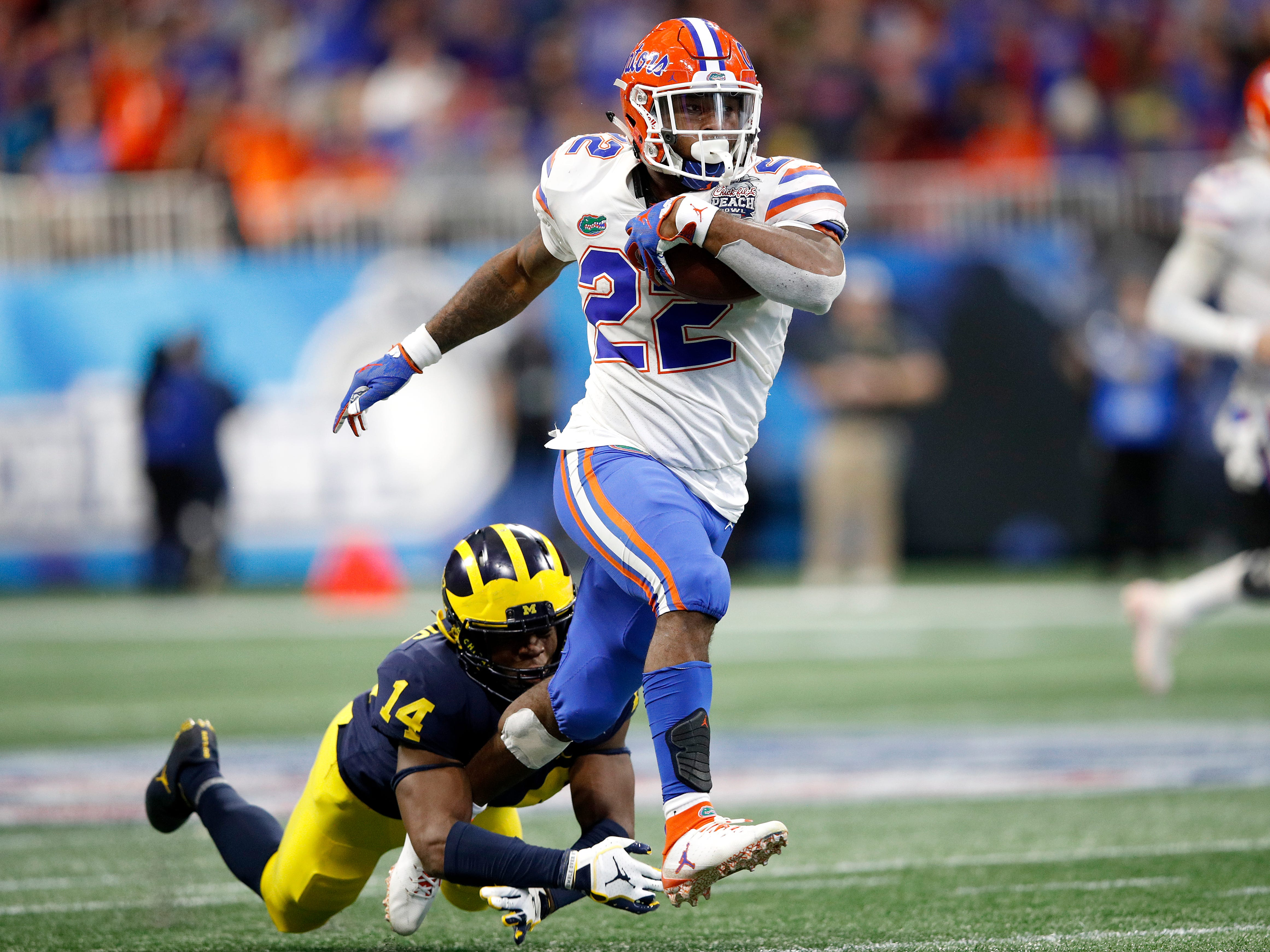 Florida running back Lamical Perine escapes the tackle attempt of Michigan's Josh Metellus and runs for a fourth quarter touchdown during the first half on Saturday, Dec. 29, 2018, in Atlanta.