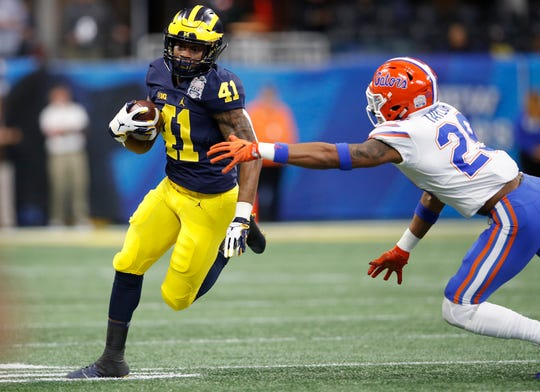 Michigan running back Christian Turner runs the ball against Florida's Jeawon Taylor during the first quarter of the Peach Bowl on Saturday, Dec. 29, 2018, in Atlanta.