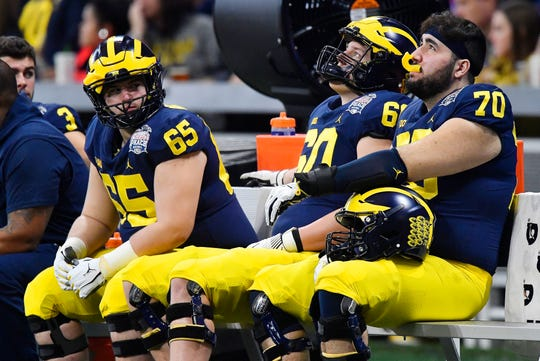 Michigan's Nolan Ulizio (70) sits on the bench with Connor Burrows (65) and Ryan Hayes (60) in the closing seconds of the Peach Bowl loss to Florida, Dec. 29, 2018, in Atlanta.