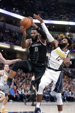Detroit Pistons center Andre Drummond (0) grabs a rebound over Indiana Pacers guard Tyreke Evans (12) during the first half of an NBA basketball game in Indianapolis on Friday, Dec. 28, 2018.