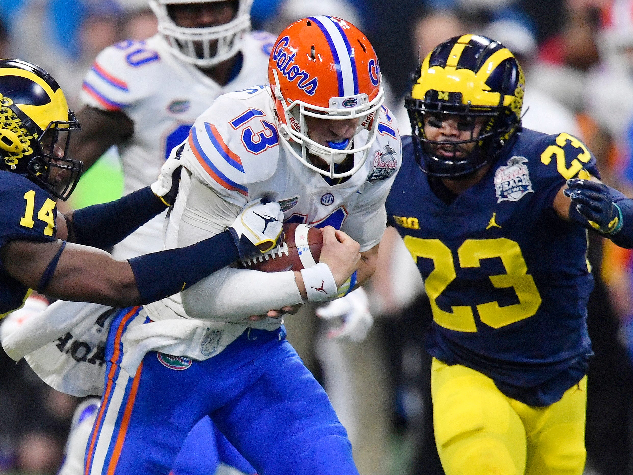 Florida quarterback Feleipe Franks runs out of the pocket against Michigan defensive back Josh Metellus during the first half of the Peach Bowl on Saturday, Dec. 29, 2018, in Atlanta.