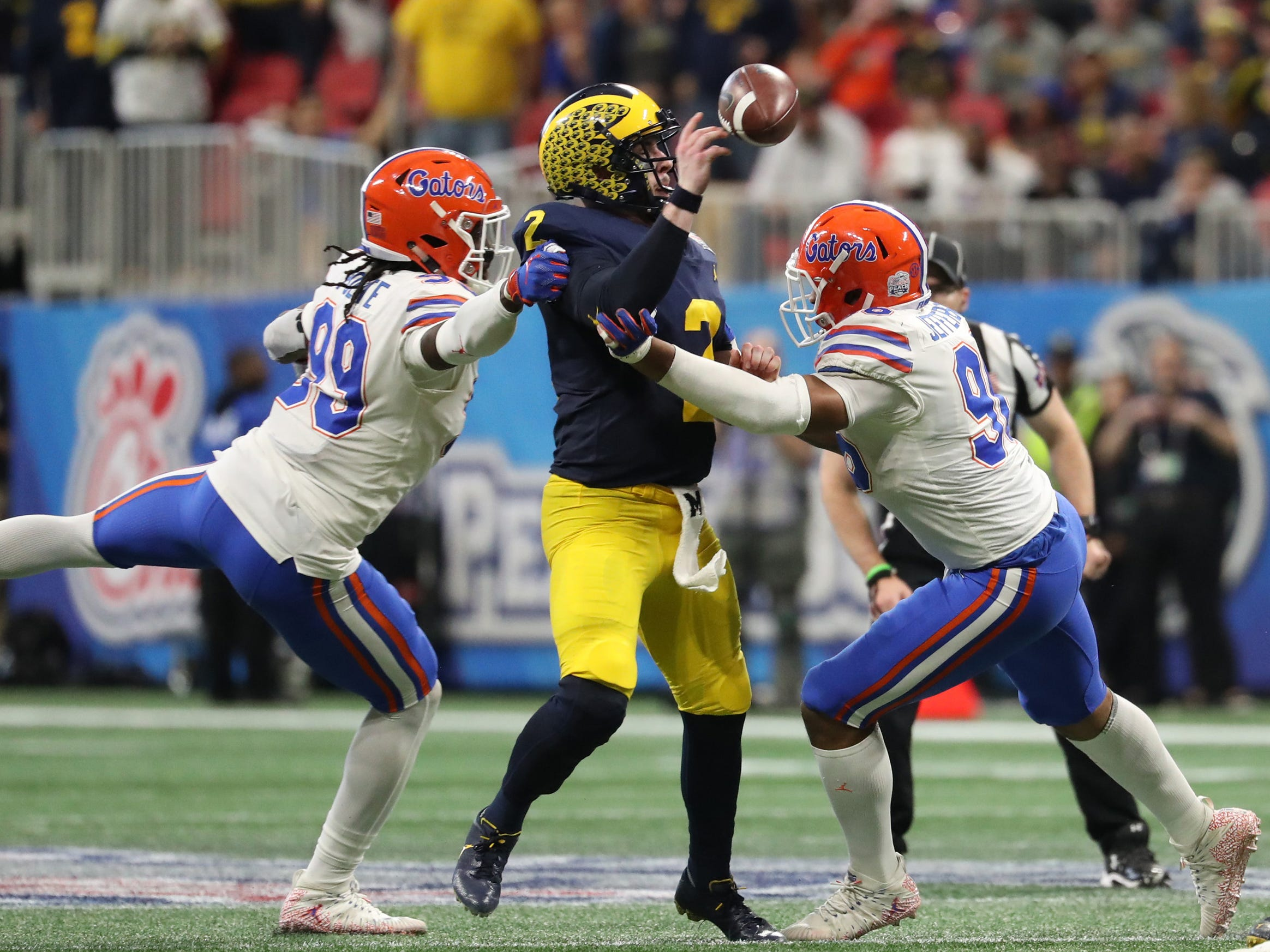 Michigan quarterback Shea Patterson fumbles the ball against Florida defensive lineman Jachai Polite, left, and defensive lineman Cece Jefferson in the second quarter of the Peach Bowl on Saturday, Dec. 29, 2018, in Atlanta.
