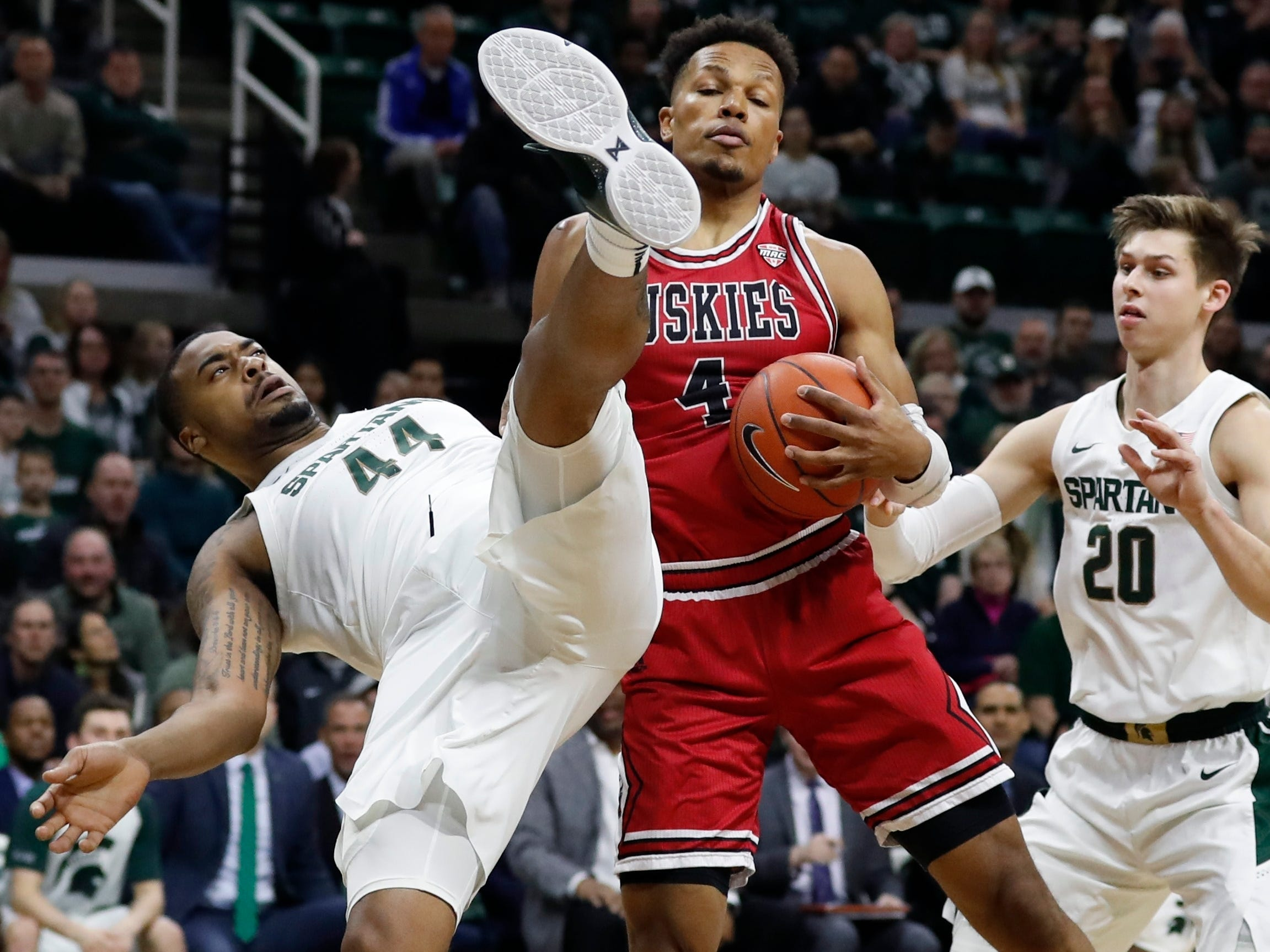Michigan State forward Nick Ward falls next to Northern Illinois forward Lacey James as they fight for the rebound during the first half on Saturday, Dec. 29, 2018, in East Lansing.