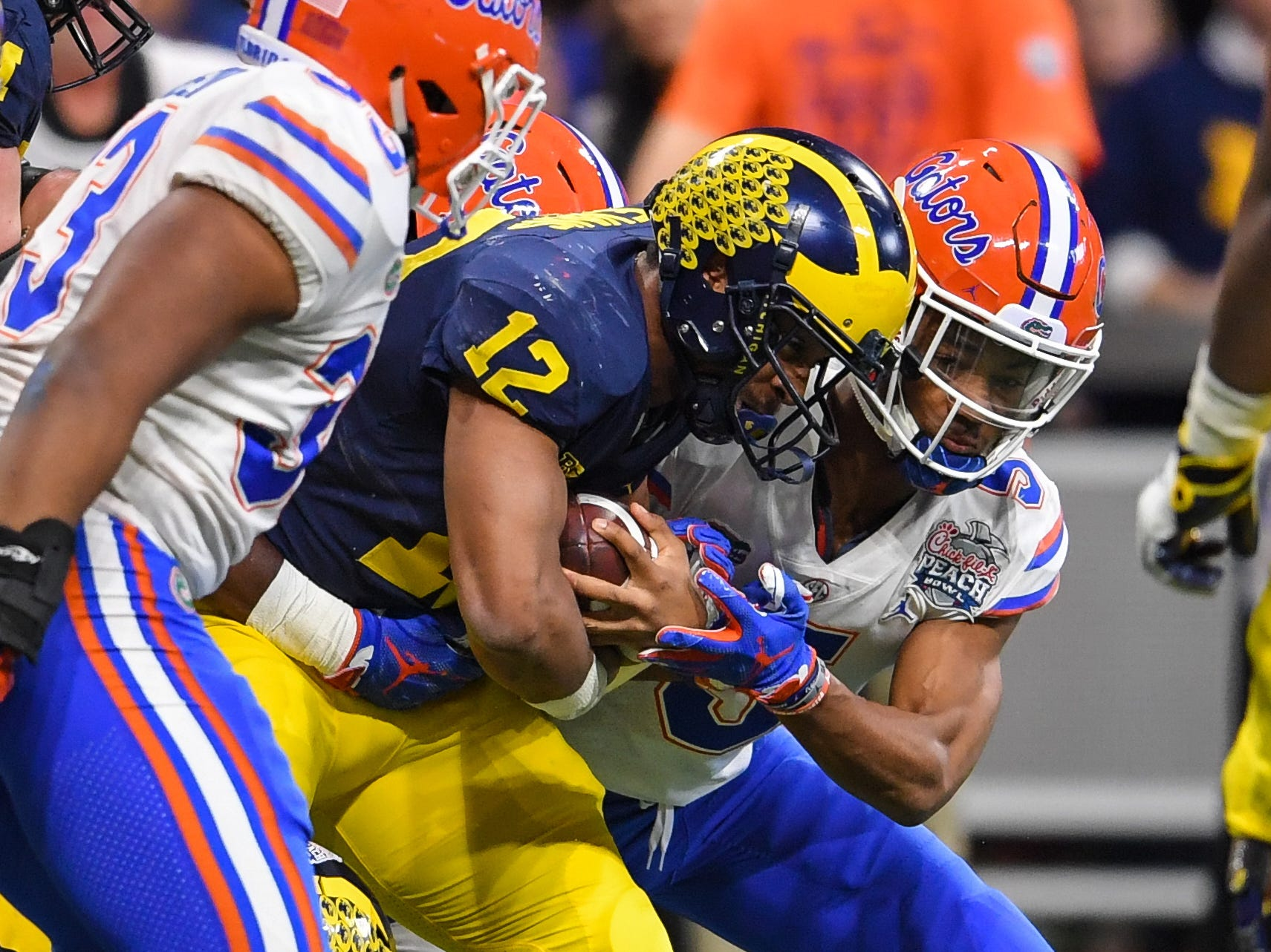 Florida defensive back CJ Henderson tackles Michigan running back Chris Evans in the first quarter of the Peach Bowl on Saturday, Dec. 29, 2018, in Atlanta.