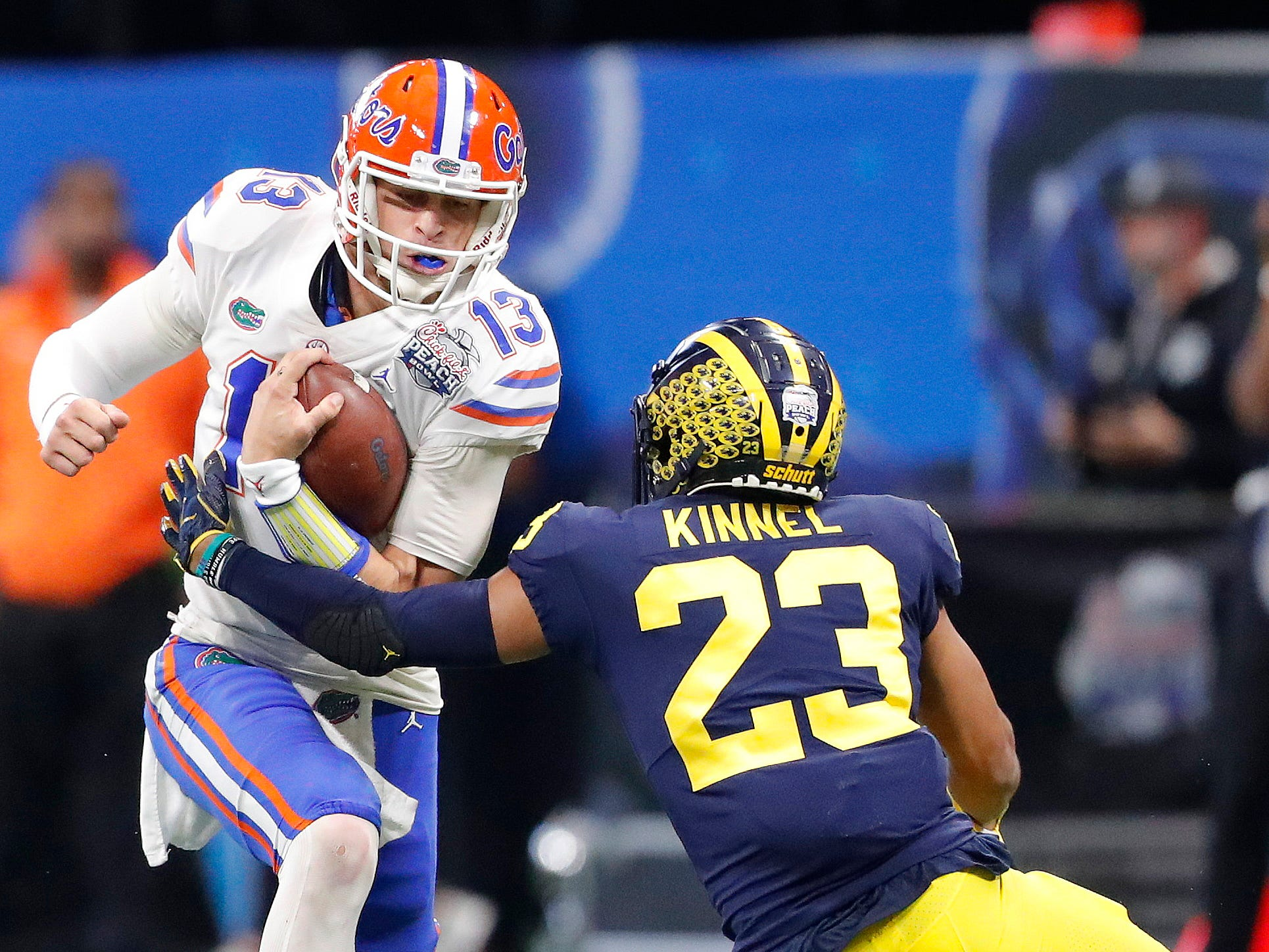 Florida quarterback Feleipe Franks runs into Michigan defensive back Tyree Kinnel during the first half of the Peach Bowl on Saturday, Dec. 29, 2018, in Atlanta.
