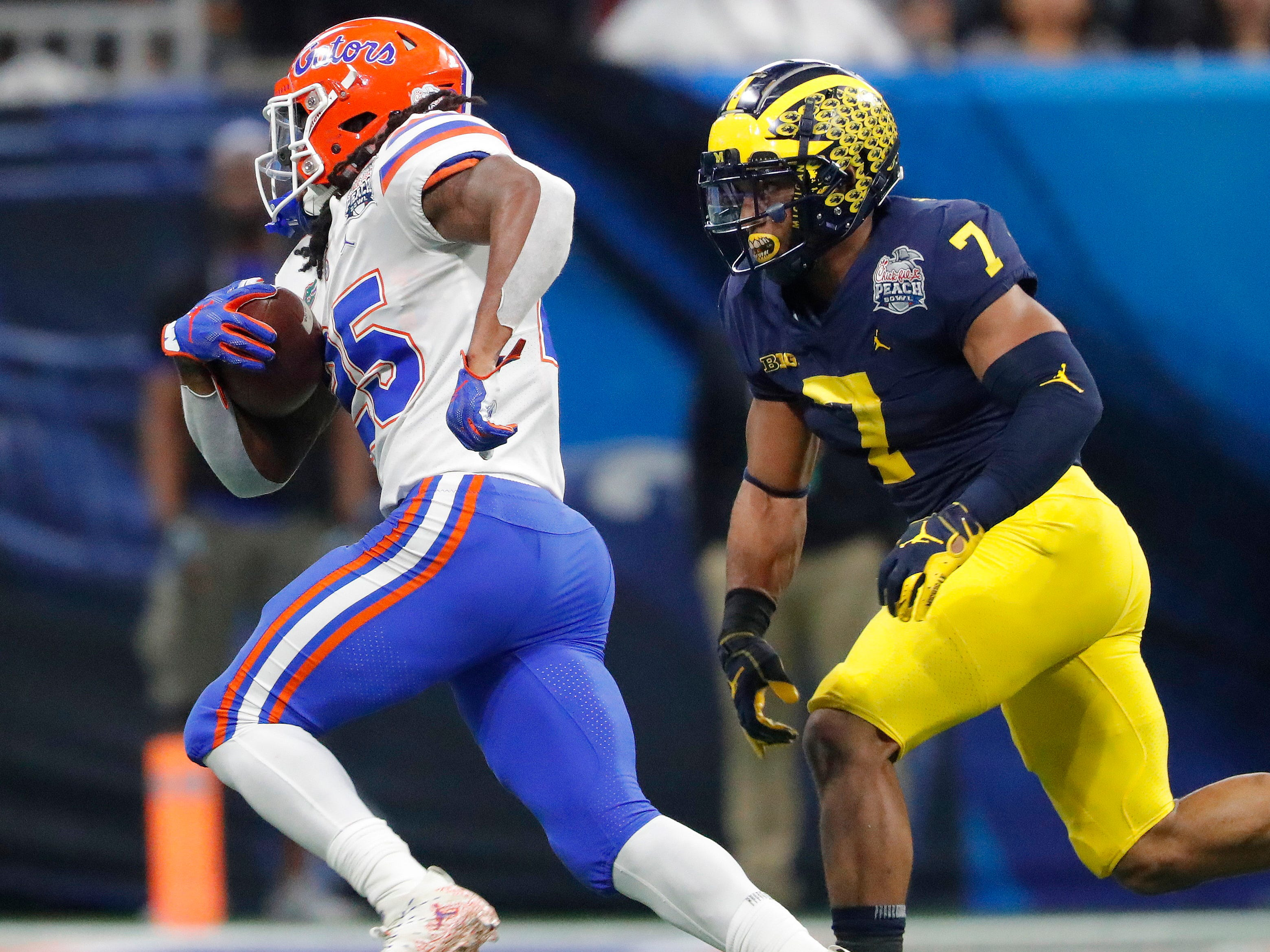 Florida running back Jordan Scarlett runs against Michigan linebacker Khaleke Hudson during the first half of the Peach Bowl on Saturday, Dec. 29, 2018, in Atlanta.