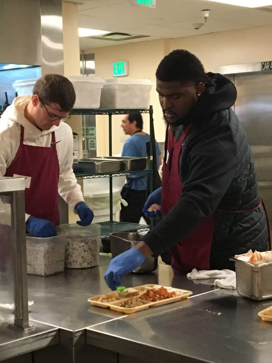 Freshman offensive lineman James Ohonba, right, puts a cupcake on a plate as Michigan State football players help serve lunch to homeless and impoverished San Francisco residents at St. Anthony's Dining Room on Saturday, Dec. 29, 2018.