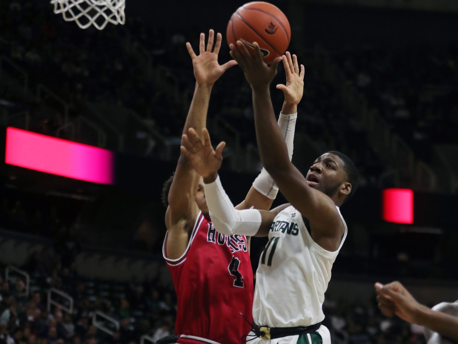 Michigan State forward Aaron Henry scores against Northern Illinois forward Lacey James during the second half Saturday, Dec. 29, 2018 at the Breslin Center in East Lansing.