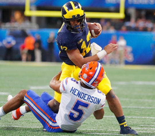 Michigan running back Chris Evans  runs into Florida defensive back CJ Henderson during the first half of the Peach Bowl on Saturday, Dec. 29, 2018, in Atlanta.
