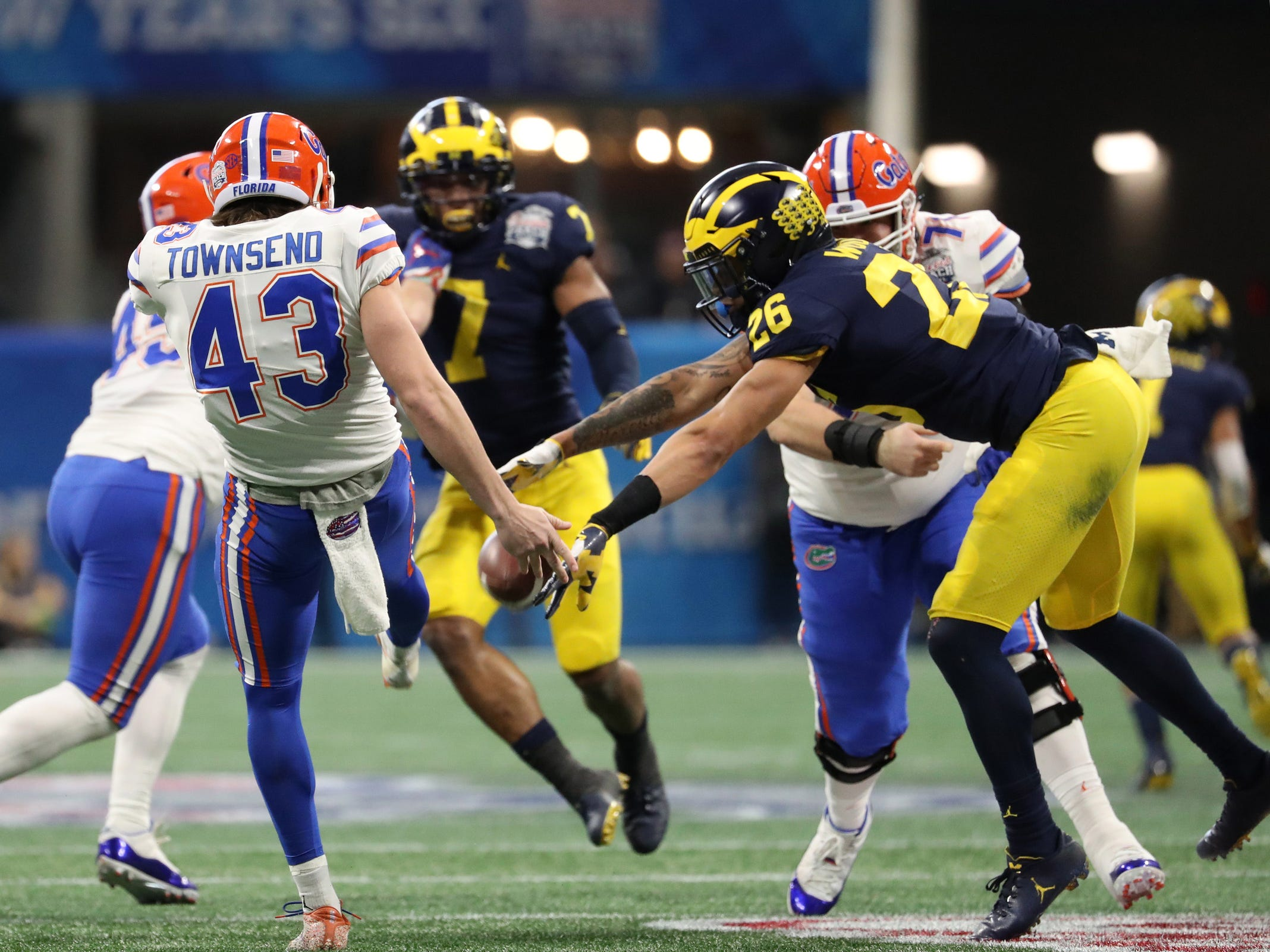 Michigan defensive back J'Marick Woods, right, blocks a punt by Florida punter Tommy Townsend in the second quarter during the Peach Bowl on Saturday, Dec. 29, 2018, in Atlanta.