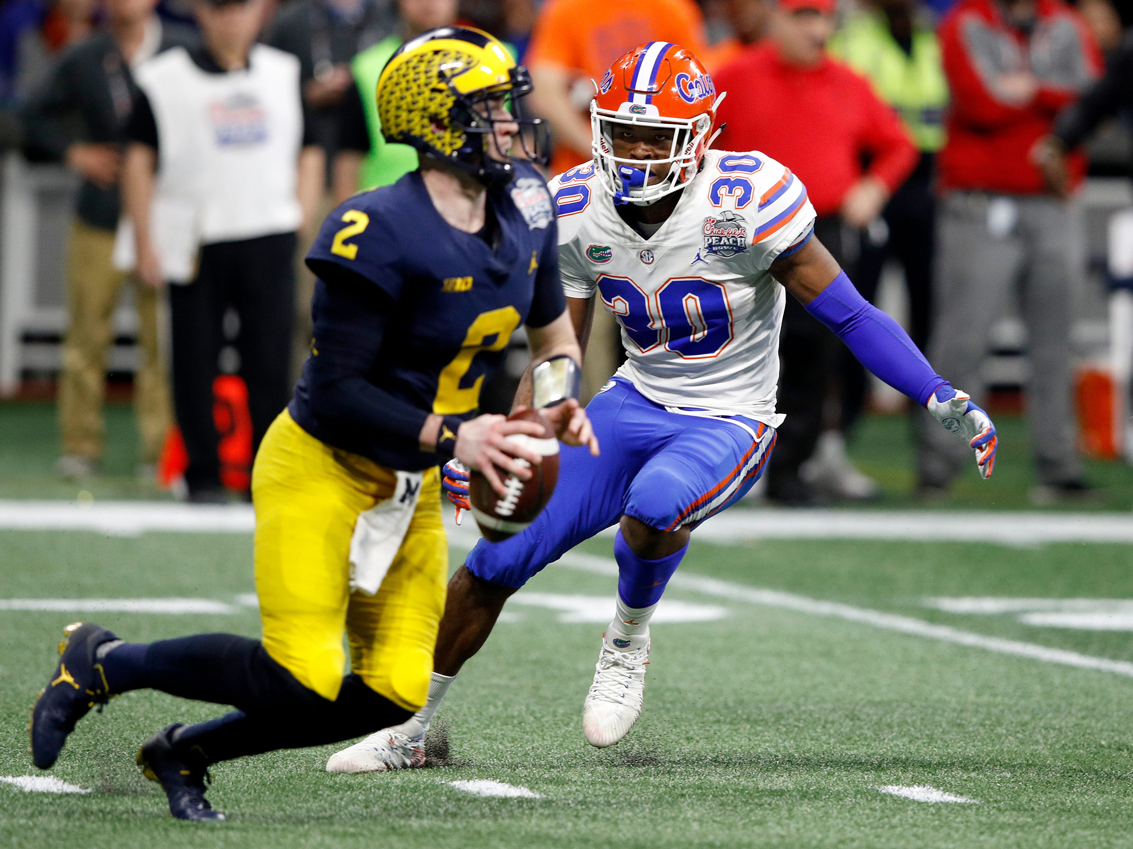 Michigan QB Shea Patterson is sacked by Florida's Amari Burney in the third quarter during the first half on Saturday, Dec. 29, 2018, in Atlanta.
