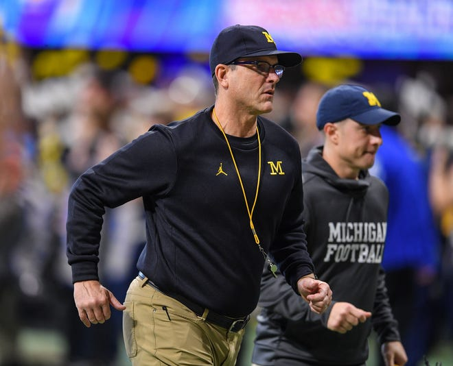 Michigan coach Jim Harbaugh runs off the field before the Peach Bowl on Saturday, Dec. 29, 2018, in Atlanta.