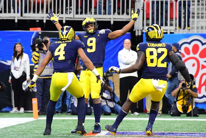 Donovan Peoples-Jones (9) of the Michigan Wolverines is congratulated by his teammates Nico Collins and Nick Eubanks after scoring a first-quarter touchdown reception against the Florida Gators.