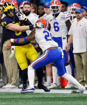 Florida defensive back Jeawon Taylor (29) tackles Michigan tight end Zach Gentry (83) during the first half.