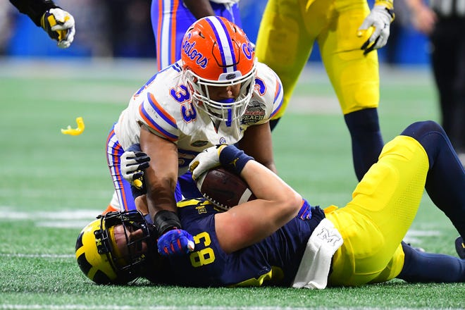 Michigan's Zach Gentry is tackled by Florida's David Reese II in the Peach Bowl.