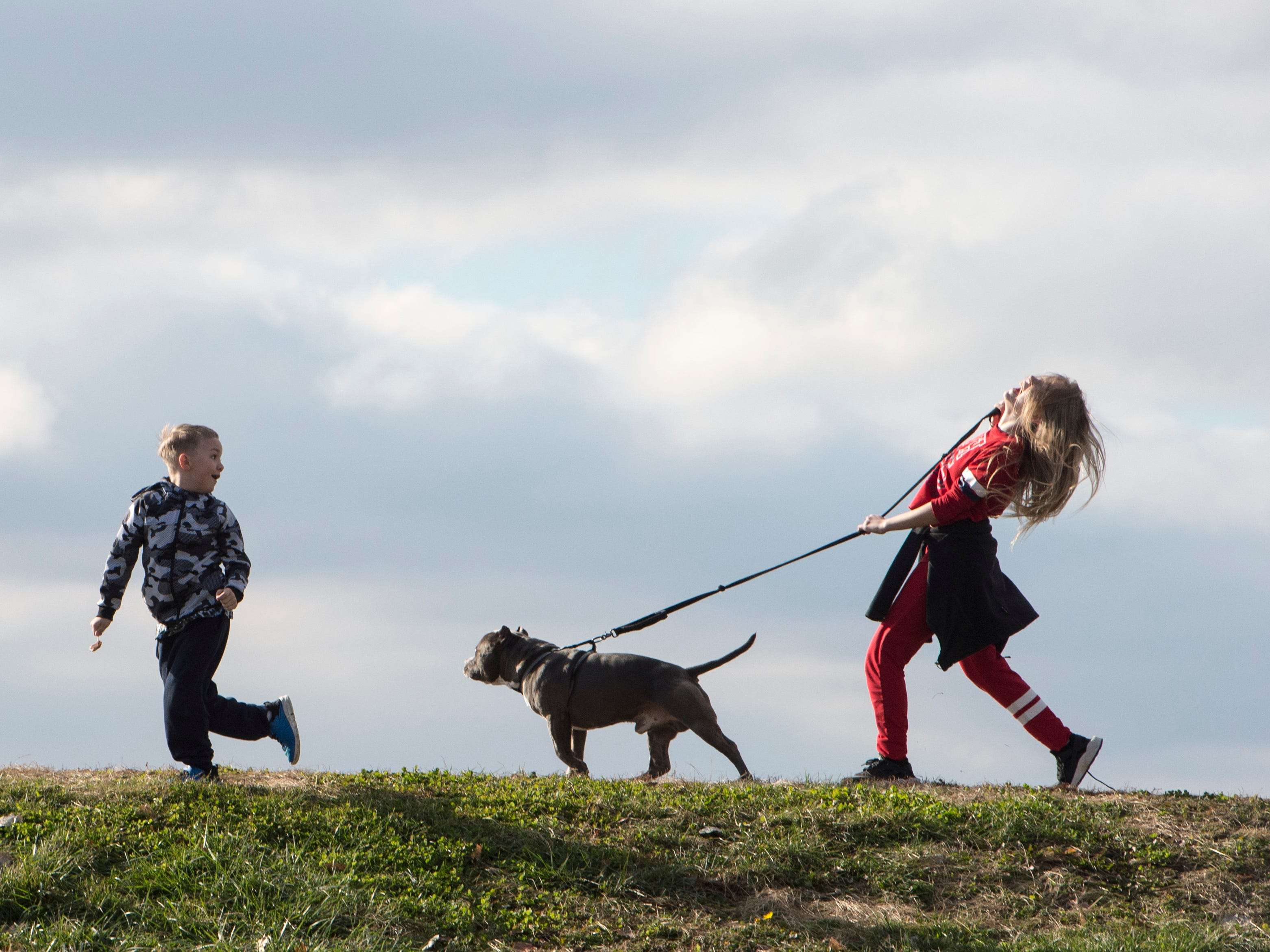 Hunter Pryor, 7, runs ahead as Kalise Vincent, 11, attempts to control their dog, Wallie, while talking a stroll down the Greenway Friday, Dec. 28, 2018.