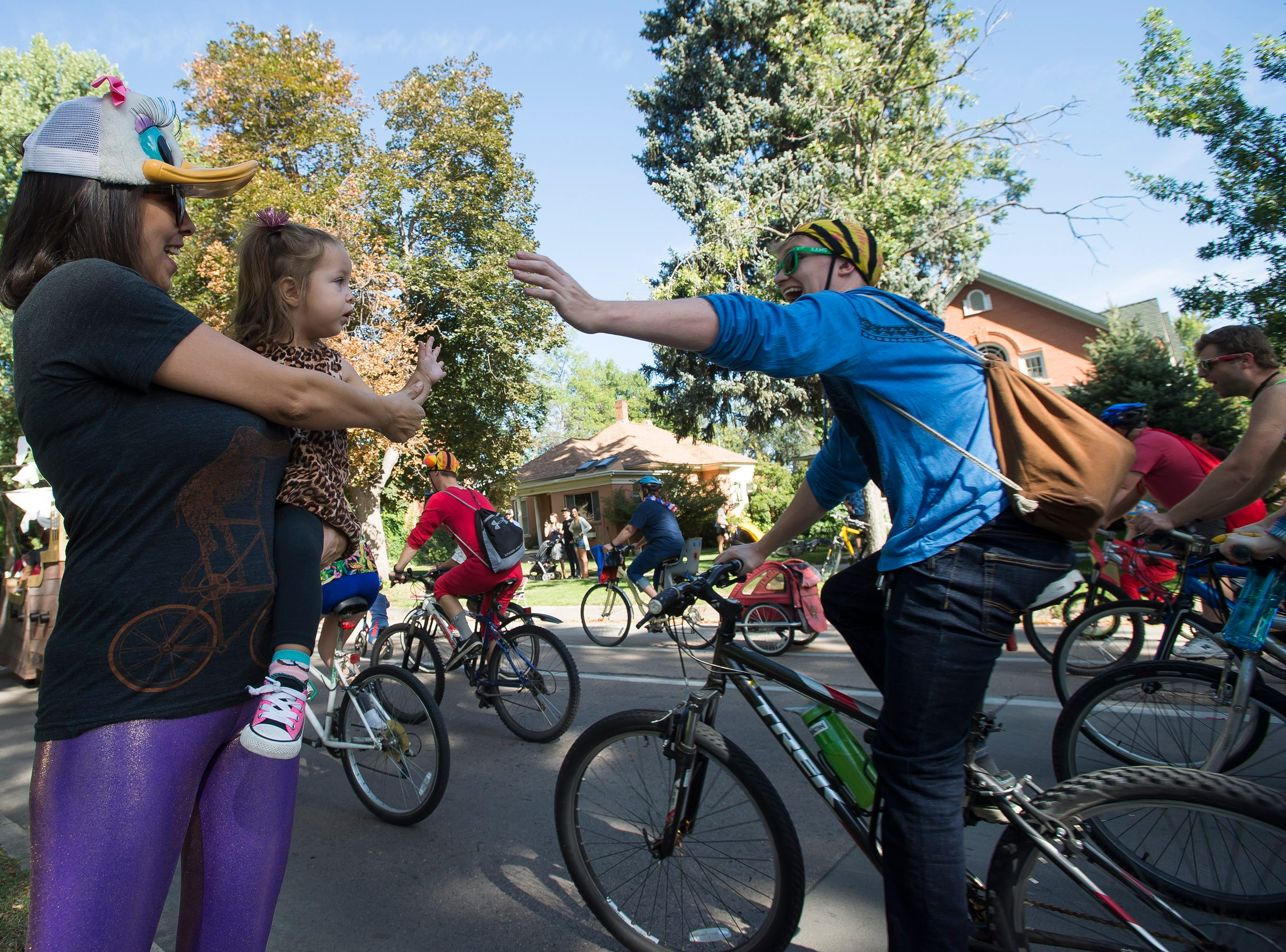 Ilana Targoff, 2, gets a high five from a rider while being held by her mother Sarah Targoff during the Tour de Fat Bike parade on Saturday, Sept. 1, 2018, in Fort Collins, Colo.