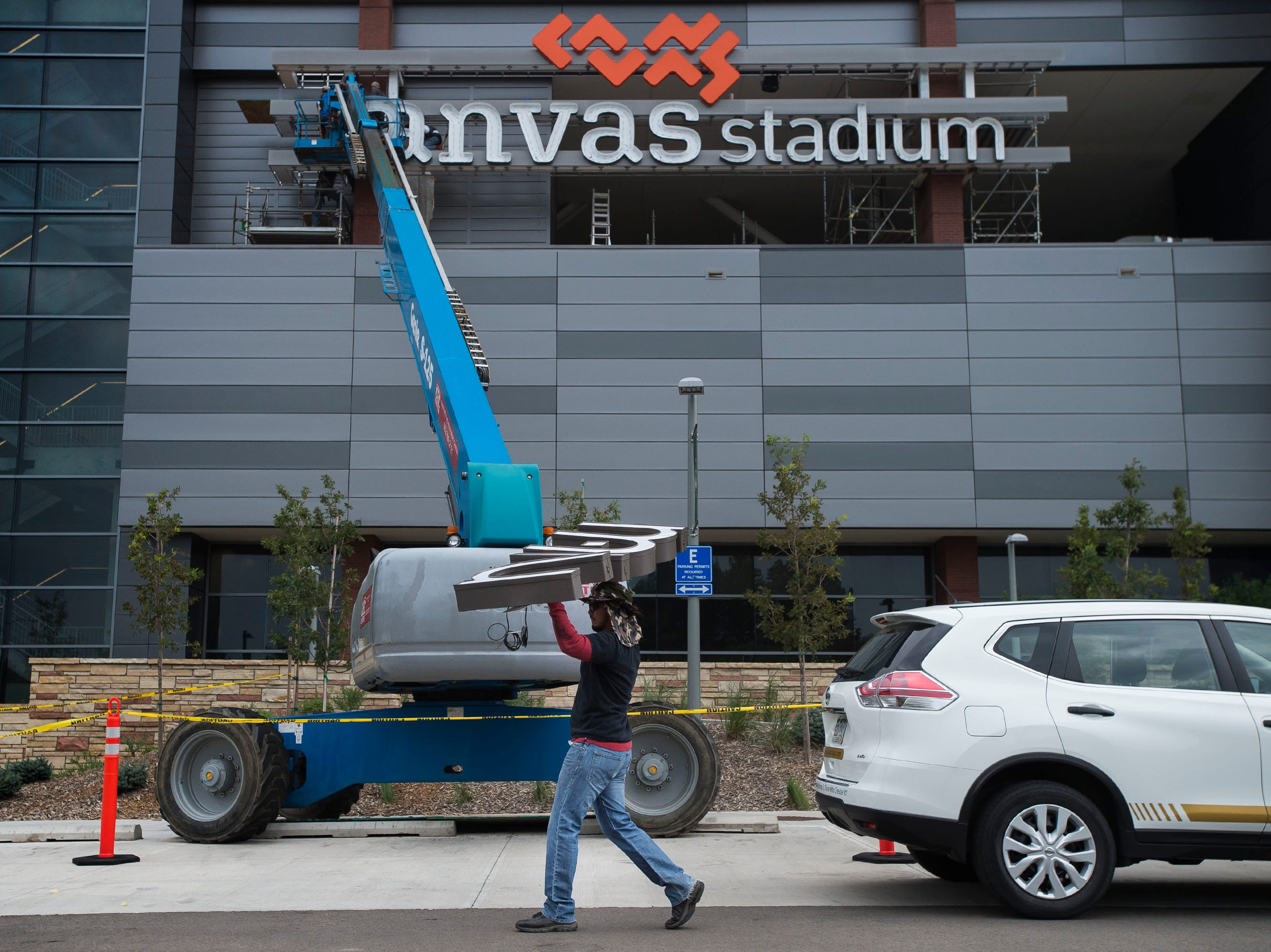DaVinci Sign Systems, Inc. employee Christopher Gonzalez carries letters to the North face of the stadium while crews work to install the West-facing Canvas Stadium logo sign onto Colorado State University's football stadium on Tuesday, Aug. 21, 2018, in Fort Collins, Colo.